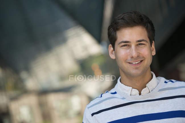 Portrait de jeune homme en pull rayé regardant à la caméra . — Photo de stock