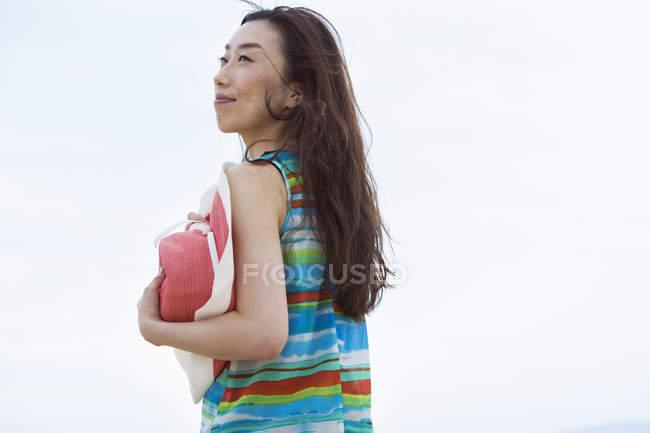 Веселий Азіатський жінка з солом'яному капелюсі стоячи на вулиці проти синього неба. — стокове фото