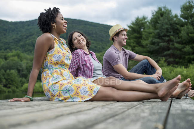 Small group of people sitting on wooden pier overlooking country lake. — Stock Photo