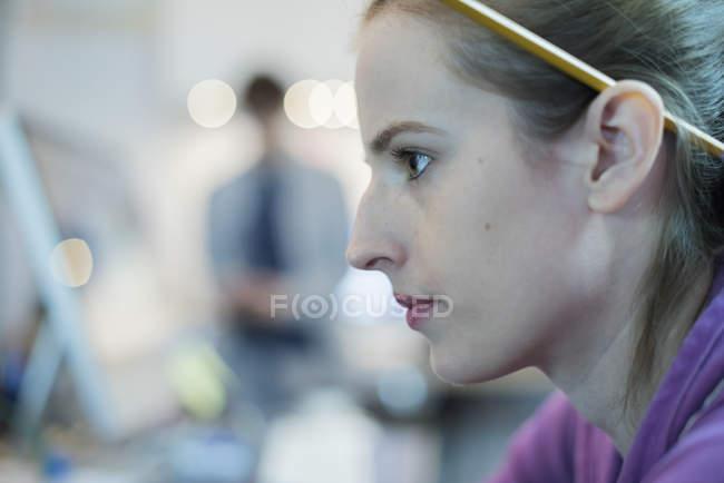 Profil de jeune femme avec un crayon derrière l'oreille. — Photo de stock
