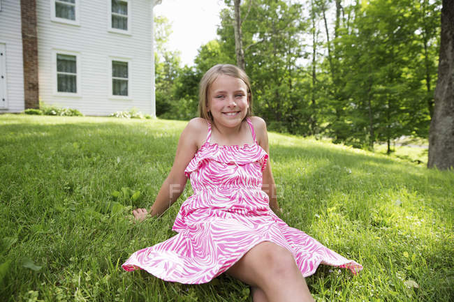 Vorpubertierendes Mädchen in pinkfarbener Dress sitzt auf Rasen im Bauerngarten. — Stockfoto