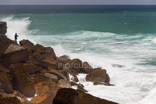 Fisherman standing on rocks of shore of Atlantic coast. — Stock Photo
