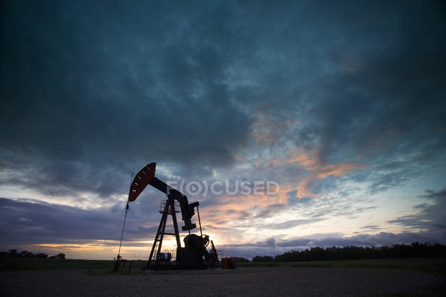 Oil derrick with well pump silhouetted against evening sky in Canada. — Stock Photo