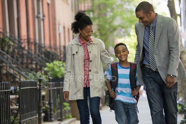 Два родителя и мальчик младшего возраста, идущие вместе по городской улице . — стоковое фото