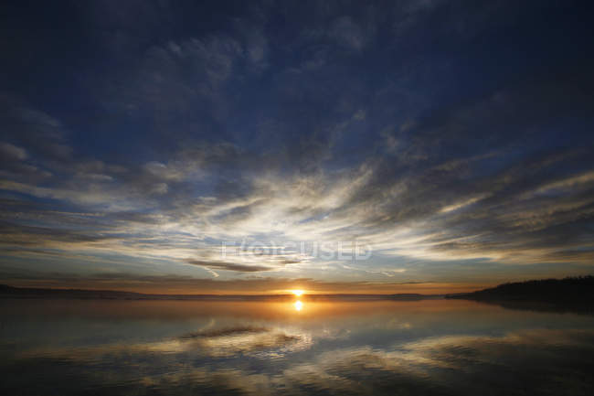 Sun on horizon over water surface of lake at dawn in Canada. — Stock Photo