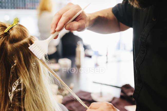 Maschio parrucchiere utilizzando pennello per tingere i capelli biondi femminili . — Foto stock