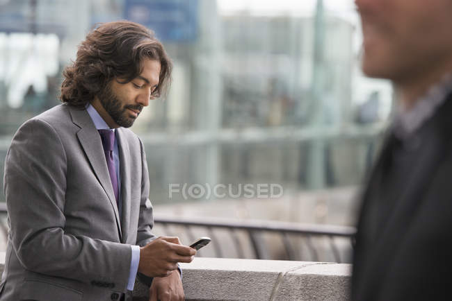 Two men in business suits on terrace with railing checking phone. — Stock Photo