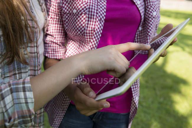 Куповані перегляд двох дівчат, торкаючись екрана Цифрова табличка з рук. — стокове фото