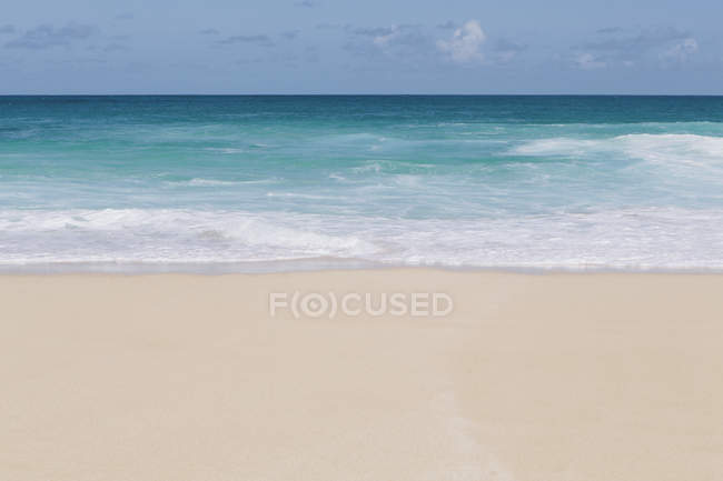 Vivid turquoise water and waves breaking on sandy beach. — Stock Photo