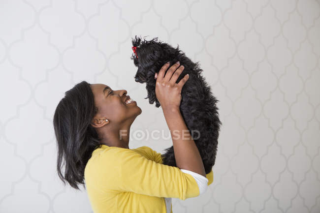 Vista laterale del cane di animale domestico piccolo nero della holding dell'adolescente — Foto stock