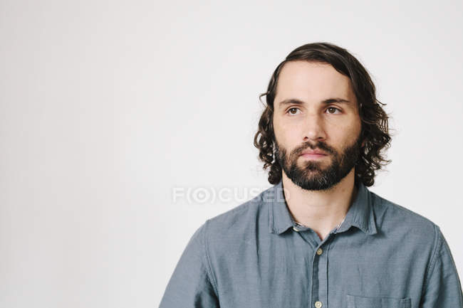 Mid adult man with beard and black hair in blue shirt, portrait. — Stock Photo