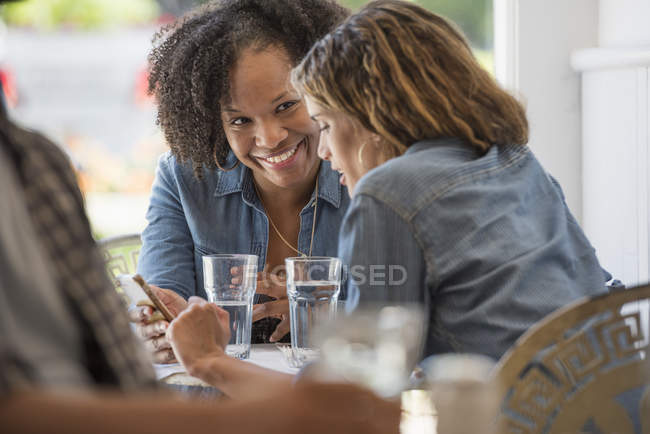 Two women talking and looking at smartphone in coffee shop interior. — Stock Photo