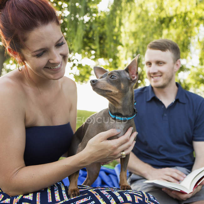 Mid adult couple resting with chihuahua pet dog in park. — Stock Photo