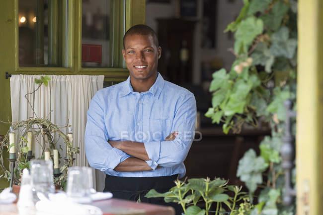 Мужчина официант, стоящий у открытого окна кафе со сложенными руками . — стоковое фото