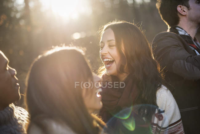 Young friends standing in sunlit forest and laughing in autumn. — Stock Photo