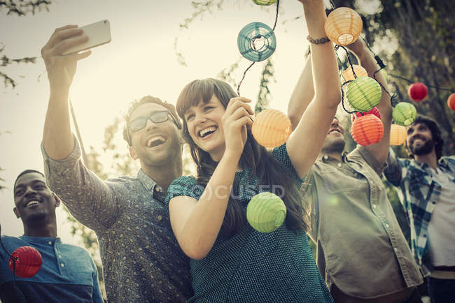 Cheerful woman and man taking selfie at party with paper lanterns outdoors. — Stock Photo