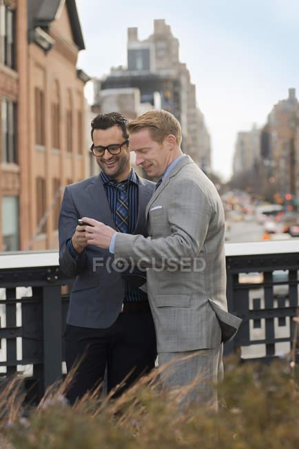 Due uomini d'affari in piedi fianco a fianco e guardando il telefono cellulare in città . — Foto stock