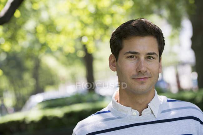 Portrait de jeune homme assis dans le parc de la ville . — Photo de stock