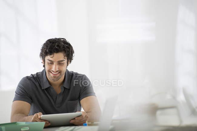 Молодий підприємець сидять і використовуючи цифровий планшет на реєстрації в office. — стокове фото