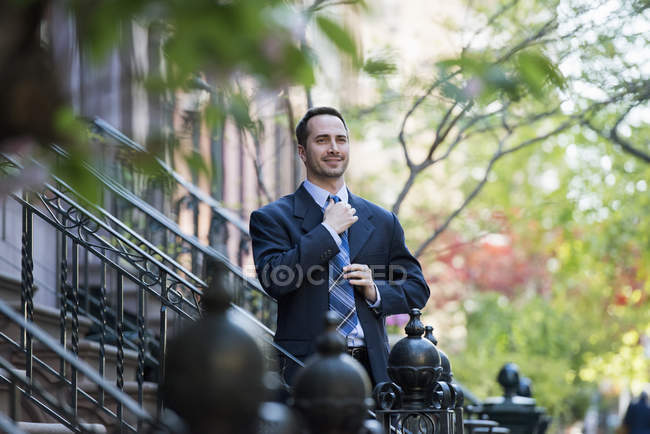 Man in business suit adjusting tie on steps of residential building on street. — Stock Photo
