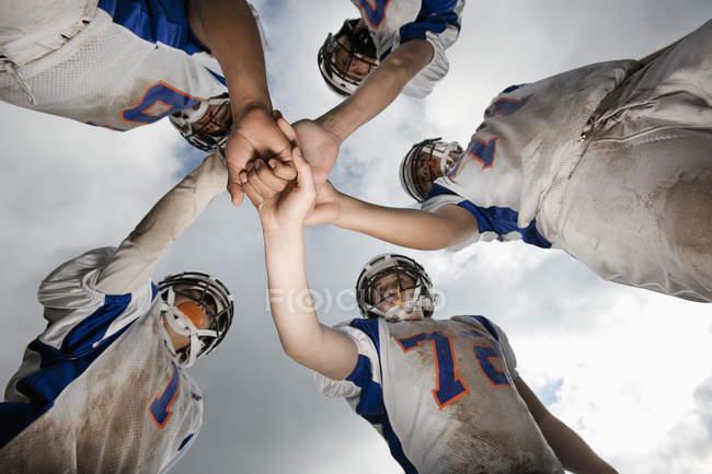 Низький кут зору групи молодих футболістів в спорт рівномірна і захисних шоломів. — стокове фото