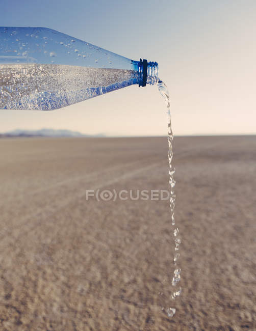 Water pouring from bottle in landscape of Black Rock Desert in Nevada — Stock Photo