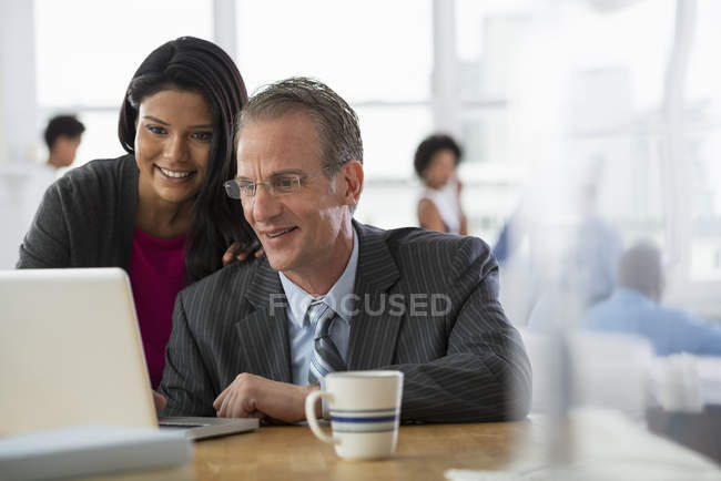 Mature man and young woman sharing laptop computer in office workplace. — Stock Photo