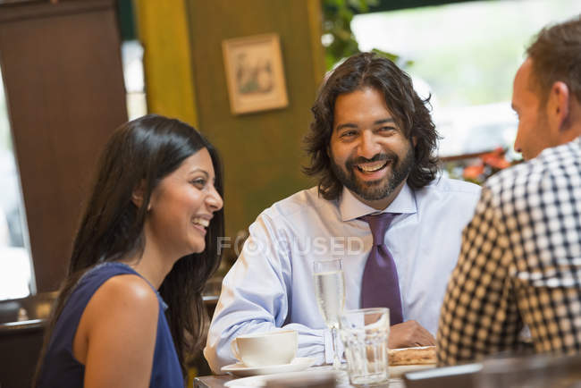 Three people sitting around table in bar and having drinks. — Stock Photo