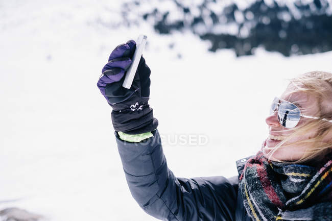 Woman holding smartphone in outstretched arm in winter. — Stock Photo