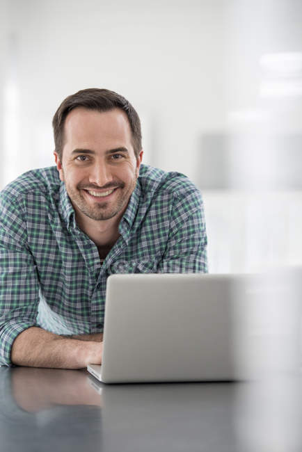 Man leaning on office table with laptop and looking in camera. — Stock Photo