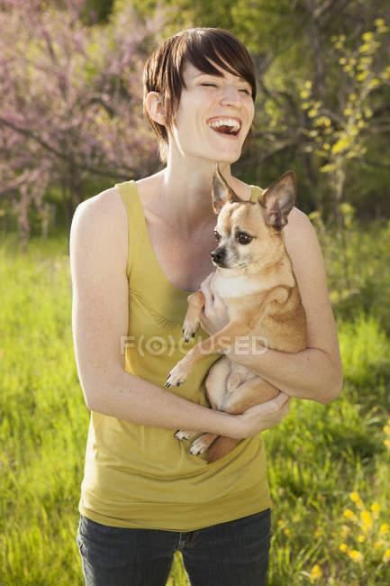 Jovem mulher no campo gramado na primavera segurando cão chihuahua confuso e rindo . — Fotografia de Stock