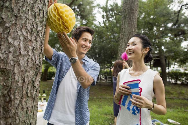 Japanese friends hanging lanterns and flags on trees in woods. — Stock Photo