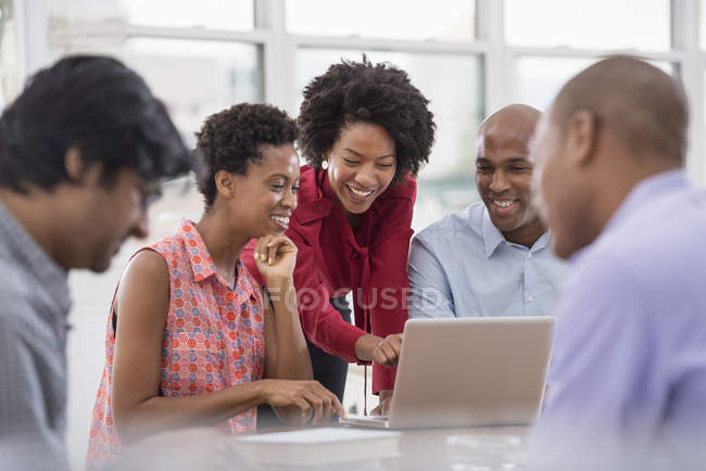 Group of colleagues using laptop together in office workplace. — Stock Photo