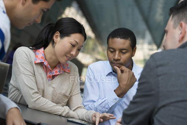 Quatro pessoas se reuniram em torno da mesa na cidade e partilha digital tablet juntos — Fotografia de Stock