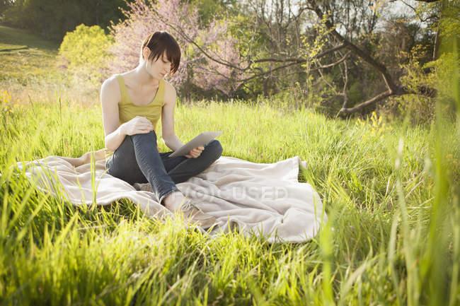 Giovane donna seduta in campo erboso su coperta e utilizzando tablet digitale . — Foto stock