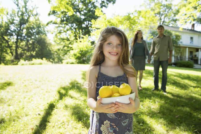 Mädchen hält Kiste von Zitronen mit Erwachsenen im Hintergrund. — Stockfoto