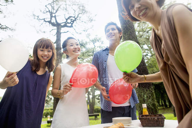 Group of friends holding balloons at outdoor party in forest. — Stock Photo