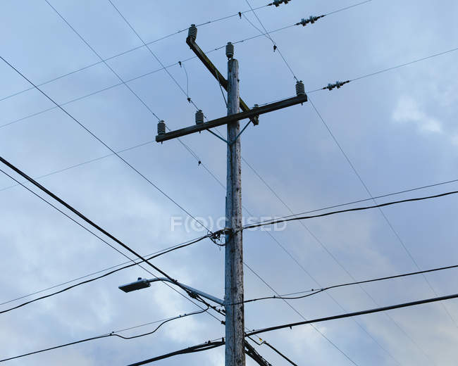 Telephone pole and electrical power lines against cloudy sky, low angle view. — Stock Photo