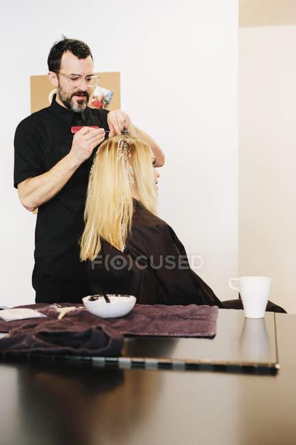 Maschio parrucchiere utilizzando stagnola mentre tingeva i capelli biondi del cliente femminile . — Foto stock