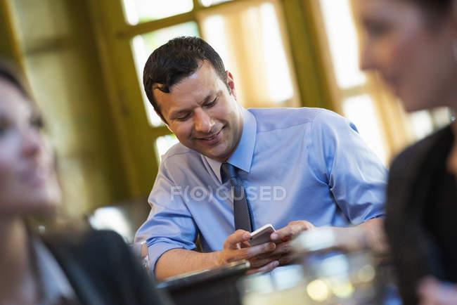 Взрослый мужчина, сидящий за столом кафе и использующий смартфон с людьми на переднем плане . — стоковое фото