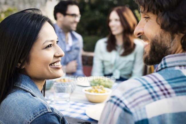 Hombre y mujer mirando al encuentro con los amigos alrededor de mesa - foto de stock