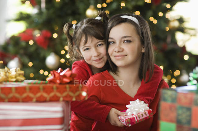 Two girls side by side by Christmas tree surrounded by presents. — Stock Photo
