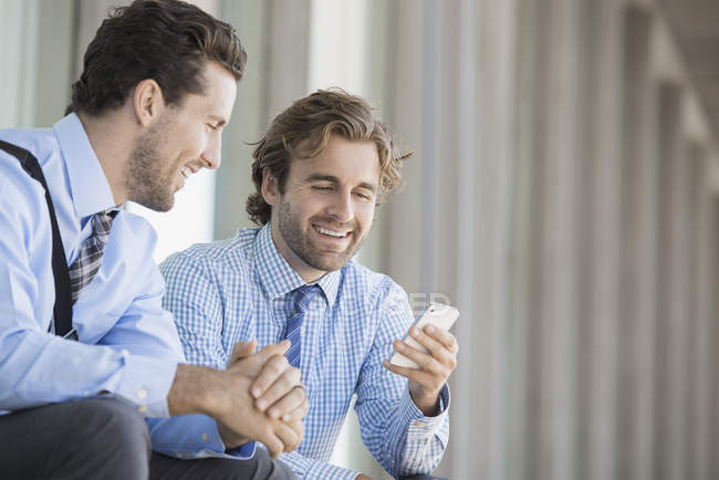 Two businessmen sitting outside office building and checking smartphone. — Stock Photo