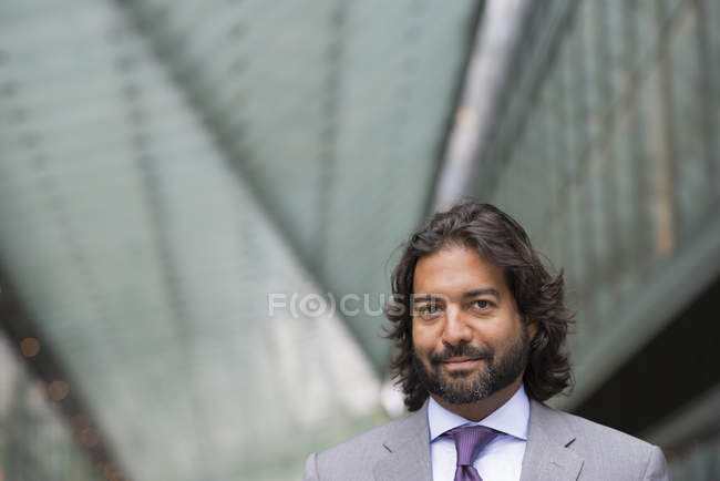 Man in business suit with beard and curly hair standing in street and looking in camera. — Stock Photo