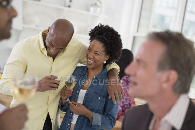 Man and woman laughing and embracing with wine glasses and people at party. — Stock Photo