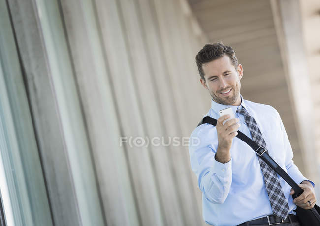 Young man with shoulder bag using smartphone outside office building. — Stock Photo