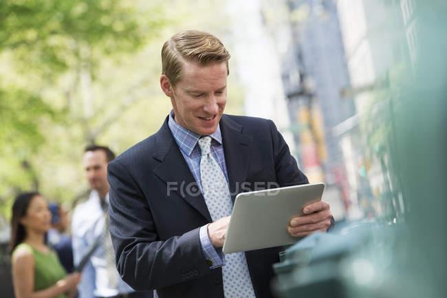 Hombre adulto medio usando tableta digital en la calle de la ciudad con pareja en segundo plano . - foto de stock