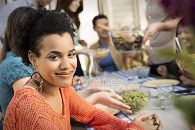 Mujer joven mirando en cámara con amigos que se reúne alrededor de la mesa y comida - foto de stock