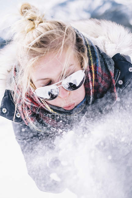 Young woman in sunglasses blowing fresh snow off hands. — Stock Photo