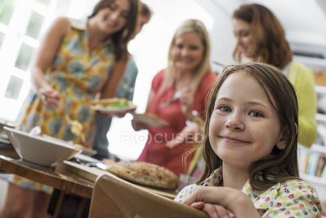 Elementary age girl looking in camera at table with adults in background. — Stock Photo